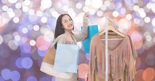 L'acquisto felice della donna dai vestiti tormenta sopra fondo vago Fotografie Stock