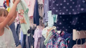 L'acquisto, i fratelli piccoli e la sorella di modo scelgono i vestiti in deposito costoso in vacanza video d archivio