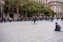 L'acrobata con il cerchio fa la prestazione al quadrato di città Immagini Stock Libere da Diritti