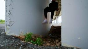 L'acrobata fa il trucco sotto il ponte, movimento lento video d archivio