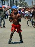 L'acrobate et le danseur sur la plage de Venise amuse les visiteurs de week-end Images stock