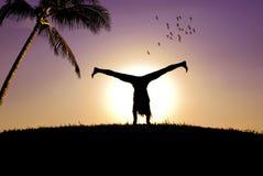L'acrobate et un coucher du soleil Images libres de droits