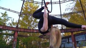 L'acrobate flexible de femme se courbe tenant ses mains derrière un anneau suspendu banque de vidéos
