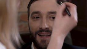 L'acteur barbu d'homme sourit tout en obtenant le maquillage avant de filmer banque de vidéos