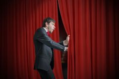L'acteur ou l'illusionniste curieux regarde derrière le rideau rouge et est étonné Image libre de droits
