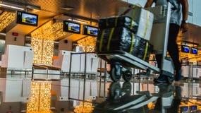 L'activité dans le terminal d'aéroport, passager avec le chariot à bagage devant le bureau de comptoir d'enregistrement Image libre de droits