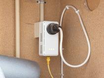 L'adaper de réseau de ligne à haute tension a branché à une prise murale Photo stock