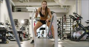 L'addestramento ad alta intensità femminile atletico di intervallo facendo uso della battaglia ropes stock footage