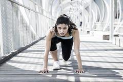 L'addestramento della donna di sport inizia sulla griglia per la corsa corrente nell'allenamento urbano di addestramento Fotografia Stock Libera da Diritti