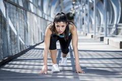 L'addestramento della donna di sport inizia sulla griglia per la corsa corrente nell'allenamento urbano di addestramento Fotografie Stock Libere da Diritti
