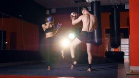 L'addestramento di kickboxing della ragazza con i guanti mezzi del fuoco Primo piano 4K archivi video