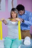 L'addestramento senior della donna con la banda di esercizio ha assistito dal fisioterapista Fotografia Stock