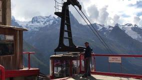 L'addetto aspetta l'ascensore aereo con i turisti nella località di soggiorno di montagna di Dombay video d archivio