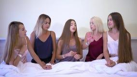 L'addio al nubilato in pigiami, cinque giovani belle amiche emozionali si diverte la conversazione sul letto nella sala dell'hote stock footage