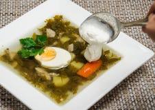 L'addition de la crème sure en soupe Photographie stock libre de droits