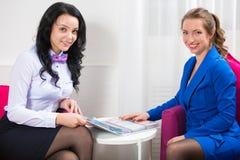 L'administrateur de salon de beauté communique avec le client Verticale de deux belles femmes image libre de droits