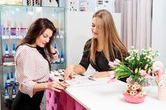 L'administrateur du salon de beauté dit la fille au client au sujet des services du salon images stock