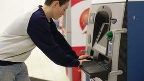 L'ado insère la carte de banque dans l'atmosphère et écrit le PIN clips vidéos