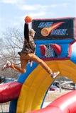 L'ado monte au-dessus du jeu de carnaval de Rim To Dunk Basketball In images libres de droits