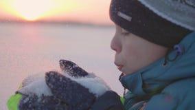 L'ado souffle des flocons de neige avec sa paume Beau coucher du soleil Amusement et jeux à l'air frais banque de vidéos