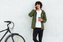 L'adolescent élégant parle par l'intermédiaire de cellulaire avec l'ami pendant la pause-café, apprécie le temps disponible, goût images libres de droits