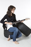 L'adolescent bascule sur la guitare se reposant sur un pneu Photo libre de droits
