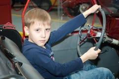 L'adolescent conduisant la voiture dans le musée de la technologie Photographie stock libre de droits