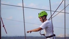 L'adolescent continue à balancer au parc de corde de faisceaux Image libre de droits