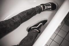 L'adolescent dans des espadrilles noires s'étend dans le bain blanc Photographie stock libre de droits