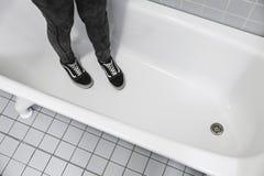 L'adolescent dans des espadrilles sportives se tient dans le bain blanc Photos libres de droits