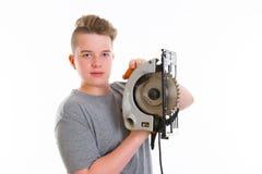 L'adolescent dans la formation professionnelle utilisant la main circulaire a vu image stock