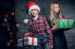 L'adolescent dans le chapeau du ` s de Santa et la fille blonde tient des boîte-cadeau Photo stock