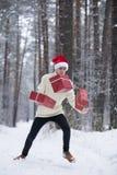 L'adolescent dans le chapeau Santa Claus rassemble des cadeaux dans une forêt neigeuse dedans Image stock