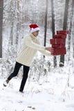 L'adolescent dans le chapeau Santa Claus rassemble des cadeaux dans une forêt neigeuse dedans Photographie stock