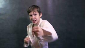 L'adolescent dans le combat de kimono remet aux poings de ondulation de karaté le mouvement lent banque de vidéos