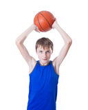 L'adolescent dans une chemise bleue jette une boule pour le basket-ball D'isolement photos stock