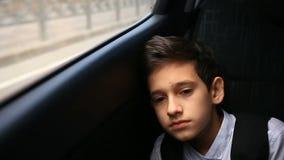 L'adolescent de garçon monte dans la voiture regardant la fenêtre En dehors de la fenêtre ont clignoté les arbres et les maisons  clips vidéos