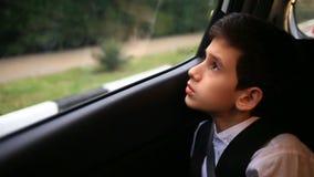 L'adolescent de garçon monte dans la voiture regardant la fenêtre En dehors de la fenêtre ont clignoté les arbres et les maisons  banque de vidéos