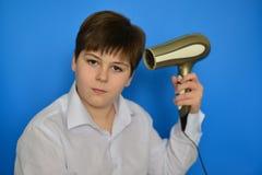 L'adolescent de garçon sèche des cheveux avec le sèche-cheveux Images stock