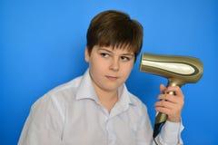 L'adolescent de garçon sèche des cheveux avec le sèche-cheveux Photo stock