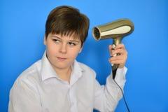 L'adolescent de garçon sèche des cheveux avec le sèche-cheveux Photo libre de droits