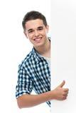 L'adolescent dirige son doigt à un panneau blanc Images stock