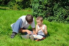 L'adolescent et l'enfant affiche le livre Image stock