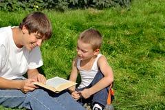 L'adolescent et l'enfant affiche le livre Images stock