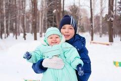 L'adolescent et le bébé garçon heureux de famille badinent en parc d'hiver Photographie stock libre de droits