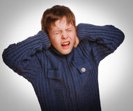 L'adolescent gris a fermé ses cris de bouche ouverts par oreilles Photographie stock