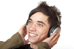 L'adolescent heureux écoute la musique par l'intermédiaire de l'écouteur Photographie stock