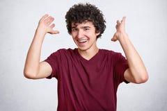 L'adolescent heureux avec les cheveux bouclés, habillés dans le T-shirt occasionnel, fait des gestes avec des mains, rit de quelq images stock