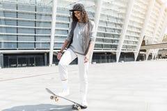 L'adolescent positif énergique monte la planche à roulettes dehors photo libre de droits