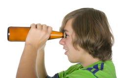 L'adolescent retient une bouteille avant des yeux Photographie stock